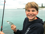 A smiling boy holding a recently caught herring