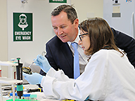 Premier and a research scientist examine an abalone in the new fish health laboratory