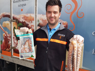 Young Achiever award winner Asher Flynn holding an octopus while standing in beside a seafood van