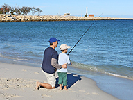 Father and son fishing on a beach
