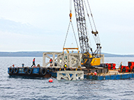 An artificial reef structure being lowered into the ocean from a barge.