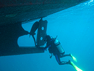 A diver surveying the hull of a large vessel