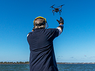 A fisheries officer prepares to catch a drone as it lands on a boat