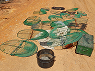 A pile of illegal fish and marron traps scattered on a dirt road