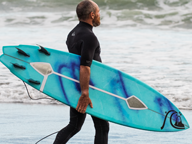 Surfer holding a surfboard with device attached while walking into the surf