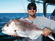 A fisherman holds a large pink snapper while on a boat
